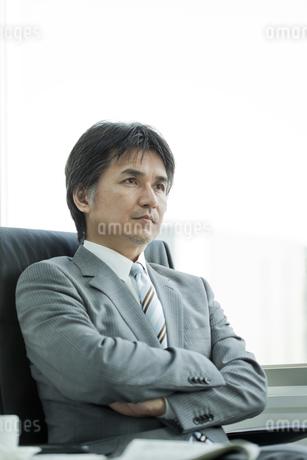 椅子に座って腕組みをする日本人ビジネスマンの写真素材 [FYI01619553]