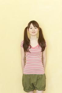 壁の前に立ち笑顔の若い日本人女性の写真素材 [FYI01619567]