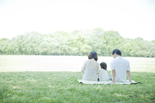 公園でシートに座り過ごす3人家族の写真素材 [FYI01619583]