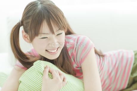 クッションを抱えて笑う若い日本人女性の写真素材 [FYI01619595]
