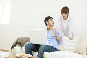 ソファでパソコンをする若い夫婦の写真素材 [FYI01619598]