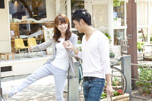 買い物をして歩く若い夫婦の写真素材 [FYI01619631]