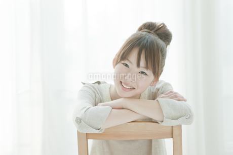 笑顔で椅子に座る若い日本人女性の写真素材 [FYI01619671]