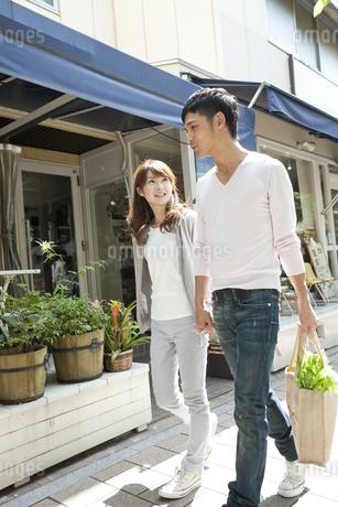 買い物をして歩く若い夫婦の写真素材 [FYI01619713]