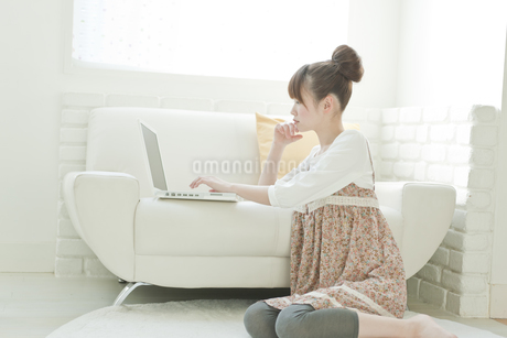 ソファーでパソコンをする若い日本人女性の写真素材 [FYI01619716]
