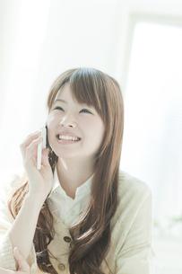机で携帯電話をかける若い日本人女性の写真素材 [FYI01619727]