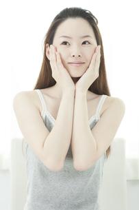 両手を頬に添えてうっとりする若い女性の写真素材 [FYI01619761]
