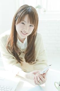 机でメールをする若い日本人女性の写真素材 [FYI01619776]