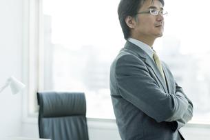 机に座り腕組みをするビジネスマンの写真素材 [FYI01619791]