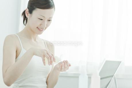 鏡の前でローションを手に持つ女性スキンケアイメージの写真素材 [FYI01619793]