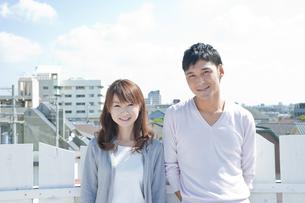 屋上に立つ若い夫婦の写真素材 [FYI01619794]
