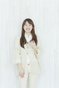 壁の前に立ち笑顔の若い日本人女性の写真素材 [FYI01619822]