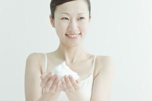 洗顔の泡を手にのせる若い女性スキンケアイメージの写真素材 [FYI01619825]