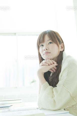 頬杖をついて見上げる若い日本人女性の写真素材 [FYI01619827]