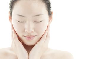 両手を頬に添える若い女性のスキンケアイメージの写真素材 [FYI01619844]
