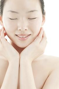両手を頬に添える若い女性のスキンケアイメージの写真素材 [FYI01619853]