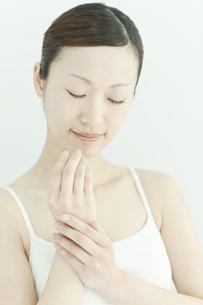 手にクリームをぬる女性のスキンケアイメージの写真素材 [FYI01619863]