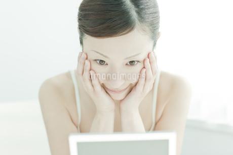 鏡の前でうるおいを実感する女性スキンケアイメージの写真素材 [FYI01619876]