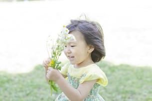 野花を持ち笑顔の女の子の写真素材 [FYI01619880]