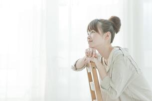 笑顔で椅子に座る若い日本人女性の写真素材 [FYI01619893]