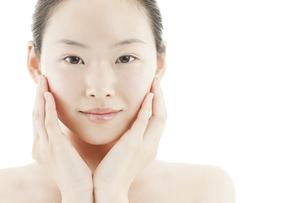 両手を頬に添える若い女性のスキンケアイメージの写真素材 [FYI01619896]