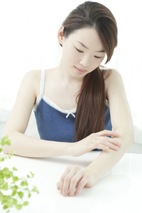 ボディローションをぬる若い女性の写真素材 [FYI01619898]