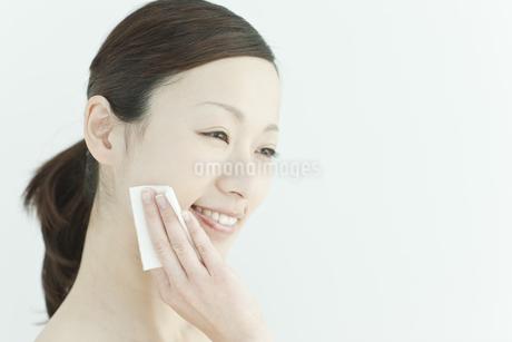 コットンで顔をふく若い女性のスキンケアイメージの写真素材 [FYI01619901]