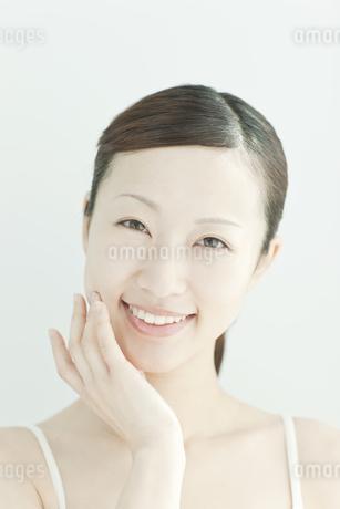 頬に指をおく女性のスキンケアイメージの写真素材 [FYI01619914]