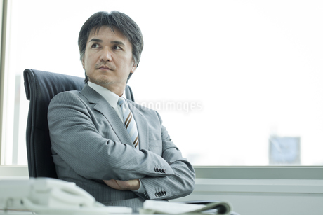 椅子に座って腕組みをする日本人ビジネスマンの写真素材 [FYI01619920]