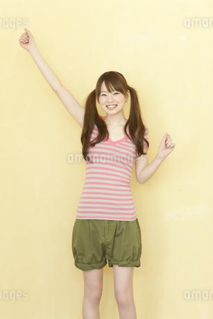 壁の前に立ち笑顔の若い日本人女性の写真素材 [FYI01619959]