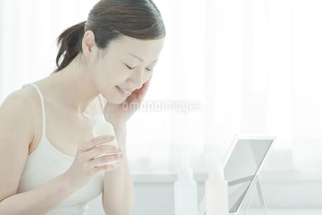 鏡の前でローションを手に持つ女性スキンケアイメージの写真素材 [FYI01619981]