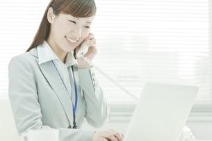 電話で話すデスクワークのビジネスウーマンの写真素材 [FYI01619992]