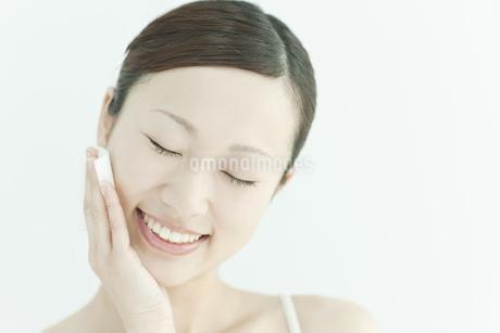 コットンで顔をふく若い女性のスキンケアイメージの写真素材 [FYI01620008]
