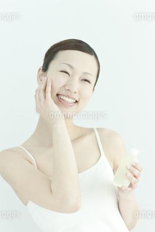 ローションを手に持つ若い女性のスキンケアイメージの写真素材 [FYI01620009]