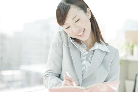 携帯電話で話しながら手帳にメモするビジネスウーマンの写真素材 [FYI01620019]