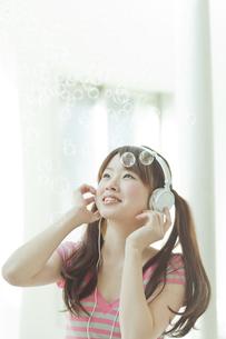 シャボン玉と音楽を楽しむ若い日本人女性の写真素材 [FYI01620025]