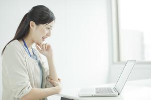 デスクでパソコンをする女性社員の写真素材 [FYI01620033]
