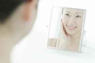 鏡の前で喜ぶ女性のスキンケアイメージの写真素材 [FYI01620035]