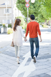 住宅街を歩く若い夫婦の写真素材 [FYI01620037]