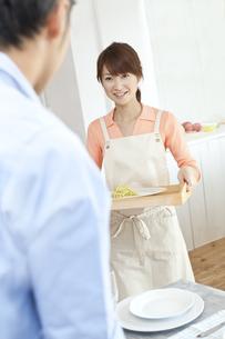食事のテーブルの準備をする若い夫婦の写真素材 [FYI01620038]