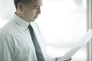 書類を見つめるビジネスマンの写真素材 [FYI01620043]