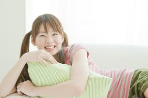 クッションを抱えて笑う若い日本人女性の写真素材 [FYI01620047]