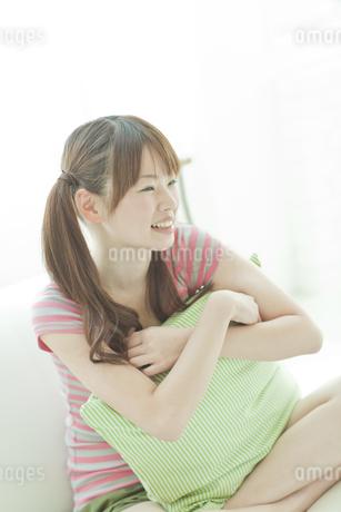 クッションを抱えて笑う若い日本人女性の写真素材 [FYI01620071]