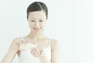 ローションを手に持つ若い女性のスキンケアイメージの写真素材 [FYI01620072]