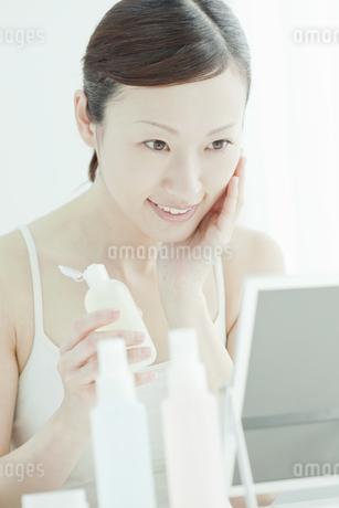 鏡の前でローションを手に持つ女性スキンケアイメージの写真素材 [FYI01620074]