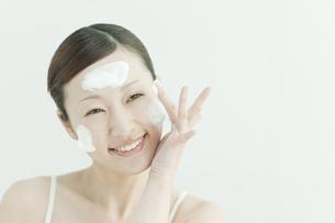 洗顔の泡を顔にのせる若い女性スキンケアイメージの写真素材 [FYI01620077]