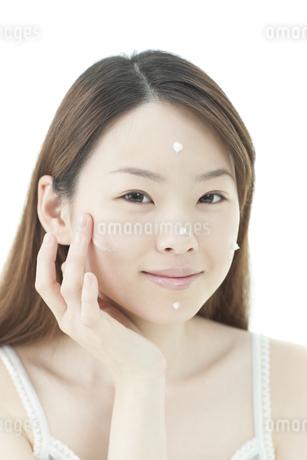 クリームをぬる若い女性の写真素材 [FYI01620092]