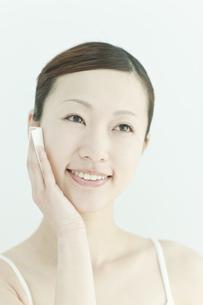 コットンで顔をふく若い女性のスキンケアイメージの写真素材 [FYI01620095]
