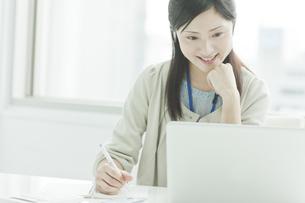パソコンを閲覧しメモする女性社員の写真素材 [FYI01620096]