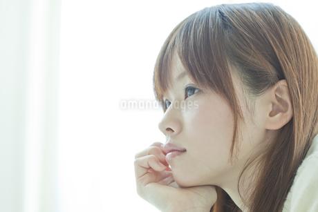 頬杖をついて考える若い日本人女性の写真素材 [FYI01620097]